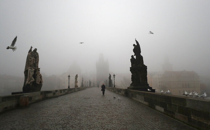 A man walks across the medieval Charles Bridge in Prague, Czech Republic, Wednesday, Feb. 24, 2021. The Czech government has decided to further tighten restrictive measures amid a surge of a highly contagious coronavirus variant in one of the hardest-hit European Union's nations. At the same time, the worsening situation has forced the Cabinet to abandon for now its plans to reopen all stores. (AP Photo/Petr David Josek)