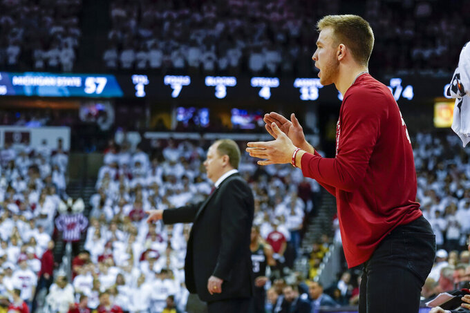 Wisconsin's Brad Davison cheers from the sidelines during the second half of an NCAA college basketball game against Michigan State, Saturday, Feb. 1, 2020, in Madison, Wis. Davison is serving a one-game suspension. Wisconsin upset Michigan State 64-63. (AP Photo/Andy Manis)