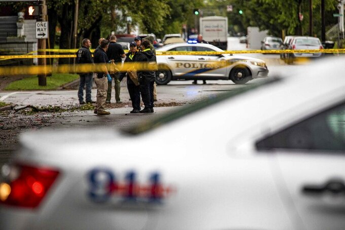 LMPD investigators stand at the corner of Dr. W.J. Hodge and W. Chestnut streets in Louisville's Russell neighborhood after a teenage boy was fatally shot and another wounded in a drive-by shooting at a bus stop Wednesday morning. Sept. 22, 2021. (Jeff Faughender/Courier Journal via AP)
