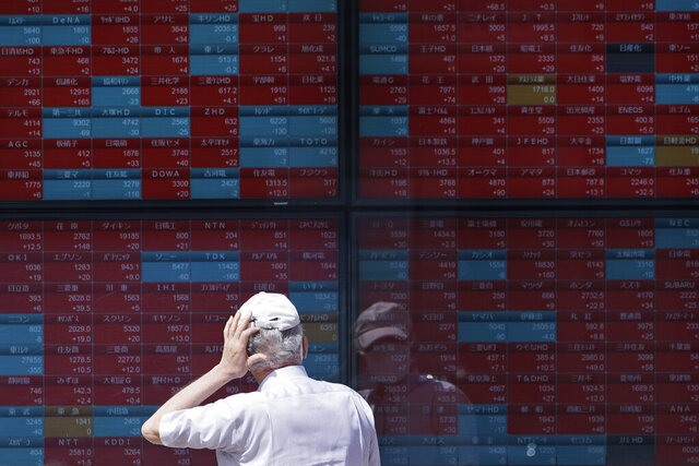 A man looks at an electronic stock board showing Japan's Nikkei 225 index at a securities firm in Tokyo Wednesday, Aug. 12, 2020. Shares were mostly lower in Asia on Wednesday after Wall Street pumped the brakes on its recent rally. (AP Photo/Eugene Hoshiko)