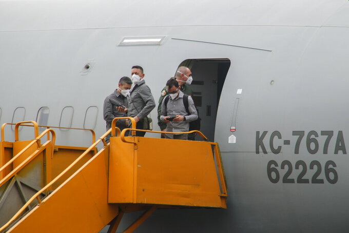 Unidentified people stand on the boarding stairs of an airplane after it arrived to transport the bodies of Italian ambassador to Congo Luca Attanasio and Carabinieri officer Vittorio Iacovacci to the capital Kinshasa, at the airport in Goma, North Kivu province, Congo Tuesday, Feb. 23, 2021. Congo has dispatched a team to support investigators on the ground in Goma where the Italian ambassador to Congo, an Italian Carabinieri police officer and their driver were ambushed and killed Monday. (AP Photo/Justin Kabumba)