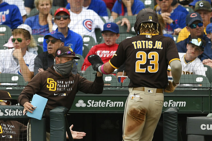 San Diego Padres' Fernando Tatis Jr. (23) celebrates with manager Jayce Tingler, left, at the dugout after scoring on a Wil Myers single during the second inning of a baseball game against the Chicago Cubs on Monday, May 31, 2021, in Chicago. (AP Photo/Paul Beaty)