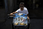 """Palestinians ride a motorcycle decorated with a poster that shows pictures of six Palestinian prisoners who escaped from an Israeli jail, their names and Arabic that reads, """"the movement of Islamic Jihad, heroes of the Gilboa prison escape,"""" at the Jenin refugee camp, in the West Bank city of Jenin, Wednesday, Sept. 8, 2021. Israel launched a massive manhunt in the country's north and the occupied West Bank early Monday after the Palestinian prisoners tunneled out of their cell and escaped from a high-security facility in the biggest prison break of its kind in decades. (AP Photo/Nasser Nasser)"""