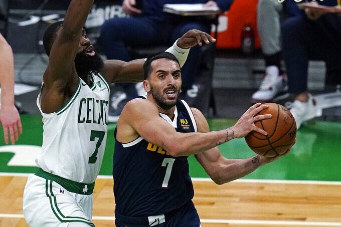 Denver Nuggets guard Facundo Campazzo, right, drives to the basket against Boston Celtics guard Jaylen Brown, left, during the first half of an NBA basketball game, Tuesday, Feb. 16, 2021, in Boston. (AP Photo/Charles Krupa)
