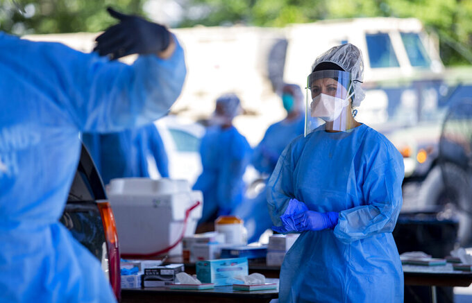 A Tidelands Health medical professional changes latex gloves during a drive-through COVID-19 testing site Friday July 17, 2020 at Myrtle Beach Pelicans Ballpark in Myrtle Beach, S.C. (Josh Bell/The Sun News via AP)
