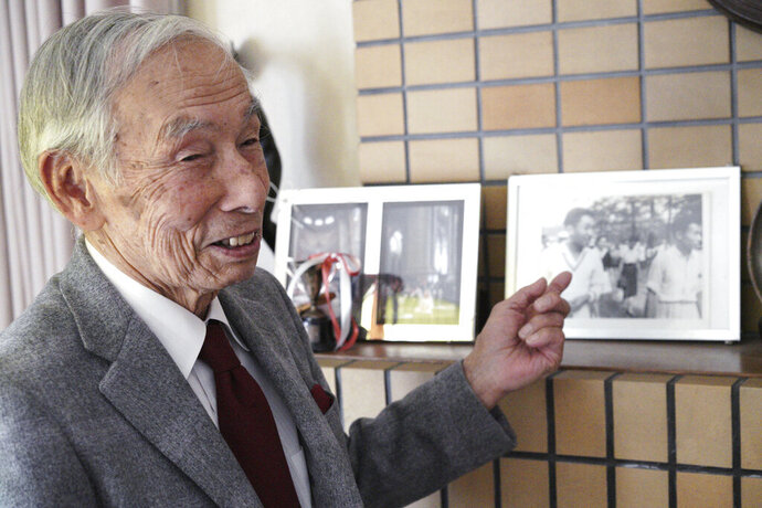 In this Feb. 3, 2019, photo, Kazuo Oda, a retired trading house executive and longtime tennis friend of Emperor Akihito, speaks on a photograph showing Oda with then Crown Price Akihito and Michiko Shoda, who become Empress Michiko, during an exclusive interview with the Associated Press in Tokyo. Akihito's Heisei era will end when he abdicates on April 30 in favor of his elder son, 58-year-old Crown Prince Naruhito, beginning a new, as yet unnamed era. (AP Photo/Eugene Hoshiko)