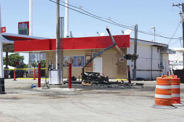 In this Monday, May 18, 2020, photo is a charred fuel pump at a gas station in Roswell, N.M. The pump was damaged when a pickup truck being pursued by a Chaves County sheriff's deputy crashed and sparked a fire. The suspect who evaded authorities remains at large after surviving an explosion at a local gas station that ended a police pursuit and injured a woman, authorities said. (Alex Ross/Roswell Daily Record via AP)