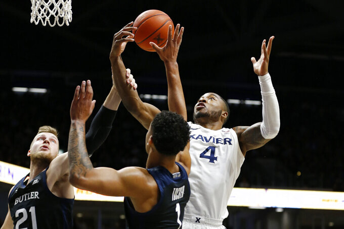 Xavier forward Tyrique Jones (4) grabs a rebound over Butler center Derrik Smits (21) and forward Jordan Tucker, front, during the first half of an NCAA college basketball game Saturday, March 7, 2020, in Cincinnati. (AP Photo/Gary Landers)