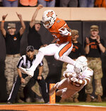 Oklahoma State wide receiver Tylan Wallace (2) jumps across the goal line while evading Texas defensive back Brandon Jones (19) in the first half of an NCAA college football game in Stillwater, Okla., Saturday, Oct. 27, 2018. (AP Photo/Brody Schmidt)