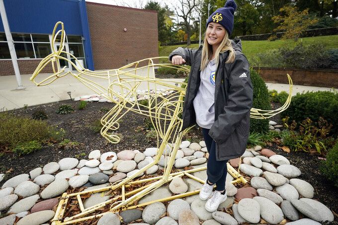 "Madison Zurmuehlen stands next to a sculpture of the University of Missouri-Kansas City's mascot outside the soccer facility in Kansas City, Mo., Friday, Oct. 23, 2020. Amid pandemic restrictions aimed at keeping students safe and healthy, colleges are scrambling to help them adjust. Zurmuehlen said daily practices, with masks, are ""the one thing I look forward to,"" so it was tough when campus sports were canceled for two weeks after an outbreak among student athletes and staff. (AP Photo/Orlin Wagner)"