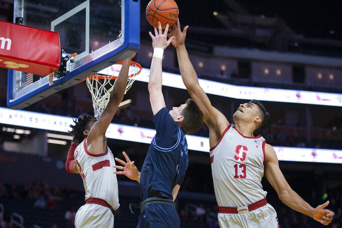 Stanford forward Oscar da Silva (13) rejects a shot by San Diego guard Finn Sullivan (5) during the first half of an NCAA college basketball game on Saturday, Dec. 21, 2019, in San Francisco. Stanford guard Bryce Wills, left, was also in on the play. (AP Photo/D. Ross Cameron)