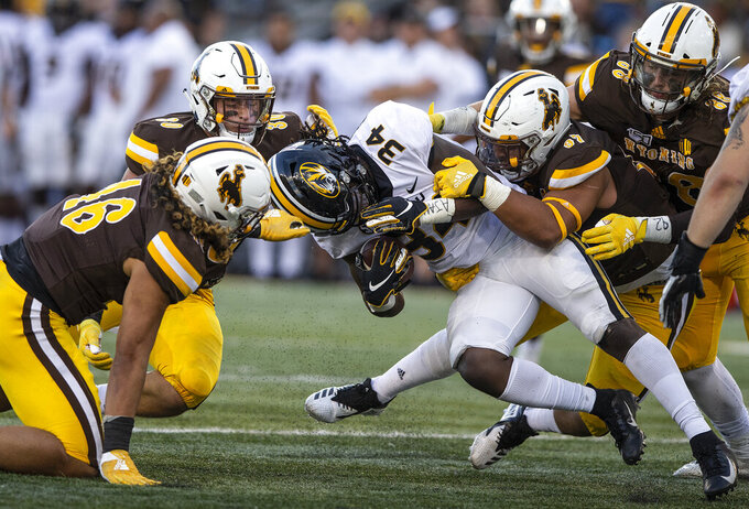 Wyoming defenders Cassh Maulia (46), Logan Wilson (30)and Mario Mora (97) tackle Missouri running back Larry Roundtree in the first quarter of an NCAA college football game Saturday, Aug. 31, 2019, in Laramie, Wy. (AP Photo/Michael Smith)