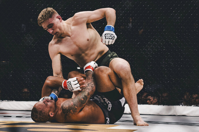 In this Feb. 16, 2019 photo, provided by Cage Fury Fighting Championships, Kyle Daukaus, top, battles Jonavin Webb during a mixed martial arts bout in Atlantic City, N.J. Daukaus was so close from signing a UFC contract when he appeared on the promotion's reality show. But the Philadelphia fighter was told he needed more work and returns to fight Saturday on the Cage Fury Fighting Championships card at Parx Casino in Bensalem, Pa.. (Nick Vespe/Cage Fury Fighting Championships via AP)