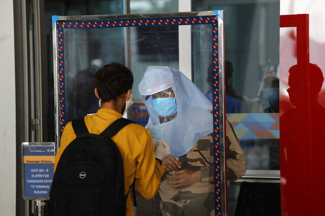 A security person standing behind a glass shield checks the identity of a passenger at the airport as domestic flights resume operations after nearly two-month lockdown amid the COVID-19 pandemic in New Delhi, India, Monday, May 25, 2020. (AP Photo/Manish Swarup)