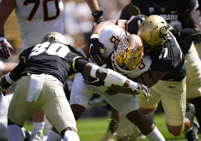 Minnesota running back Ky Thomas, center, is stopped after a short gain by Colorado safety Curtis Appleton II, left, and defensive end Blayne Toll in the second half of an NCAA college football game Saturday, Sept. 18, 2021, in Boulder, Colo. Minnesota won 30-0. (AP Photo/David Zalubowski)