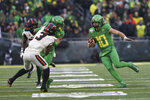 Oregon wide receiver Johnny Johnson III (3) tries to hold off Oregon State defensive backs Jaydon Grant (3) and Jalen Moore (33) to clear the way for Oregon quarterback Justin Herbert (10) during the second half of an NCAA college football game in Eugene, Ore., Saturday, Nov. 30, 2019. (AP Photo/Amanda Loman)