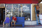 As store windows are prepped with plywood a couple waits for their automobile in Nags Head, N.C., Wednesday, Sept. 12, 2018, as Hurricane Florence approaches the coast of the Carolinas. The National Weather Service says Hurricane Florence