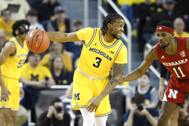 Michigan guard Zavier Simpson, left, dribbles next to Nebraska guard Dachon Burke Jr. during the first half of an NCAA college basketball game Thursday, March 5, 2020, in Ann Arbor, Mich. (AP Photo/Jose Juarez)