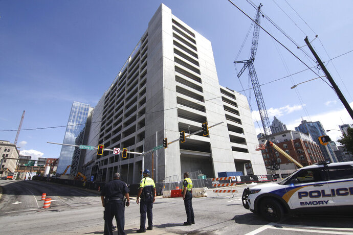 "Emergency personnel respond to the parking garage that partially collapsed on Saturday, Sept. 12, 2020.  The parking deck under construction has collapsed for a second time in as many days. Atlanta Fire Rescue said Saturday,  that fire units were deployed to the building in the city's Midtown section for ""a second major collapse"" of the parking deck that partially fell Friday.  (Steve Schaefer/Atlanta Journal-Constitution via AP)"