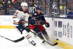 Columbus Blue Jackets' Riley Nash, right, clears the puck past Edmonton Oilers' Markus Granlund, of Finland, during the second period of an NHL hockey game Wednesday, Oct. 30, 2019, in Columbus, Ohio. (AP Photo/Jay LaPrete)