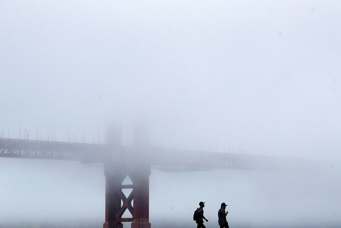 A man wears a face mask while walking on a pier in front of the Golden Gate Bridge during the coronavirus outbreak in San Francisco, Saturday, May 16, 2020. (AP Photo/Jeff Chiu)