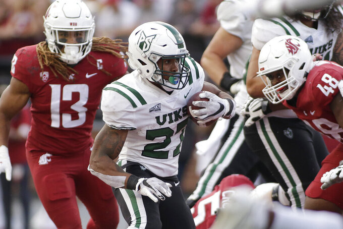 Portland State running back Malik Walker, center, carries the ball during the second half of an NCAA college football game against Washington State, Saturday, Sept. 11, 2021, in Pullman, Wash. (AP Photo/Young Kwak)