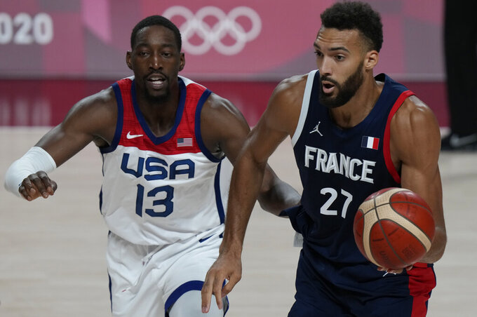 France's Rudy Gobert (27) drives ahead of United States' Bam Adebayo (13) during men's basketball gold medal game at the 2020 Summer Olympics, Saturday, Aug. 7, 2021, in Saitama, Japan. (AP Photo/Luca Bruno)