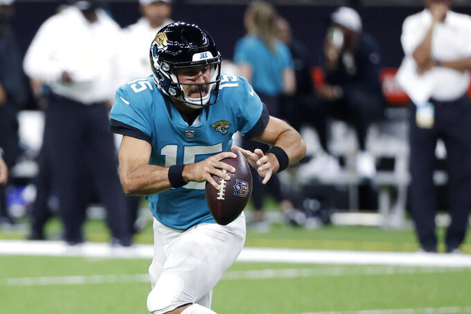 Jacksonville Jaguars quarterback Gardner Minshew (15) scrambles in the second half of an NFL preseason football game against the New Orleans Saints in New Orleans, Monday, Aug. 23, 2021. (AP Photo/Derick Hingle)