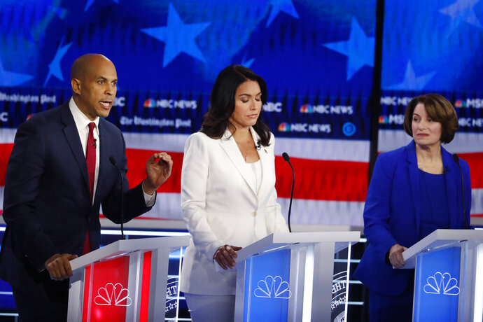 Democratic presidential candidate Sen. Cory Booker, D-N.J., left, speaks as Democratic presidential candidate Rep. Tulsi Gabbard, D-Hawaii, and Democratic presidential candidate Sen. Amy Klobuchar, D-Minn., listen during a Democratic presidential primary debate, Wednesday, Nov. 20, 2019, in Atlanta. (AP Photo/John Bazemore)