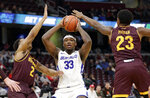 Buffalo's Nick Perkins (33) looks to pass against Central Michigan's Shawn Roundtree (2) and Dallas Morgan (23) during the first half of an NCAA college basketball game in the semifinals of the Mid-American Conference men's tournament Friday, March 15, 2019, in Cleveland. (AP Photo/Tony Dejak)