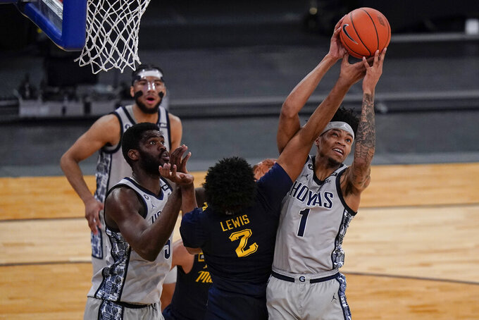 Georgetown's Jamorko Pickett (1) fights for control of the ball with Marquette's Justin Lewis (2) during the first half of an NCAA college basketball game in the Big East conference tournament Wednesday, March 10, 2021, in New York. (AP Photo/Frank Franklin II)