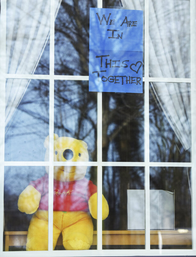 A sign reading We Are In This Together and a Winnie the Pooh bear are pictured Tuesday, April 7, 2020, in the window of the Maud Preston Palenske Memorial Library in St. Joseph, Mich. The library remains closed due to the COVID-19 pandemic. (Don Campbell/The Herald-Palladium via AP)
