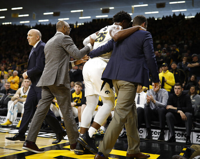 Iowa forward Tyler Cook is helped off the court after an injury during the second half of an NCAA college basketball game against Ohio State, Saturday, Jan. 12, 2019, in Iowa City, Iowa. Iowa won 72-62. (AP Photo/Matthew Putney)