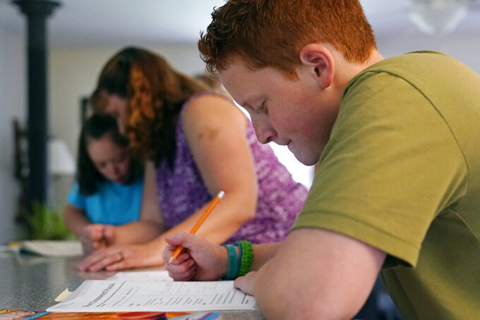 """Noah Osgood, 12, right, works on a review sheet as his mother, Jennifer, helps his sister, Lily, at their home in Fairfax, Vt., on Tuesday, July 20, 2021. """"He told me he was learning so much more at home than he ever did in school,'' Jennifer says. """"He said, 'School is just so chaotic -- we don't get very much done in any particular class. Here, I sit down, you tell me what to do, and minutes later I'm done.'"""" (AP Photo/Charles Krupa)"""