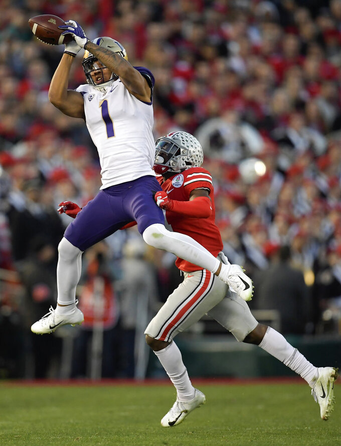 Washington tight end Hunter Bryant catches a pass over Ohio State safety Jordan Fuller during the second half of the Rose Bowl NCAA college football game Tuesday, Jan. 1, 2019, in Pasadena, Calif. (AP Photo/Mark J. Terrill)