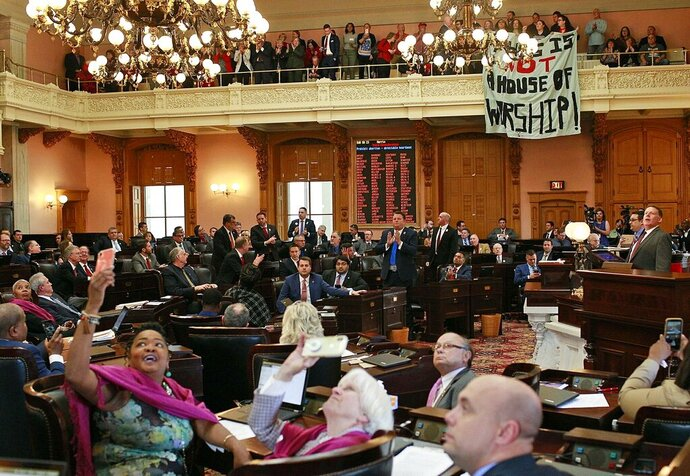 FILE - In this April 10, 2019 file photo, some members of the Ohio House applaud following their vote while others photograph protestors who unfurled banners reading