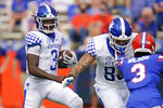 Kentucky quarterback Terry Wilson, left, looks for room to run as tight end Keaton Upshaw, center, blocks Florida defensive back Marco Wilson, right, during the first half of an NCAA college football game, Saturday, Nov. 28, 2020, in Gainesville, Fla. (AP Photo/John Raoux)