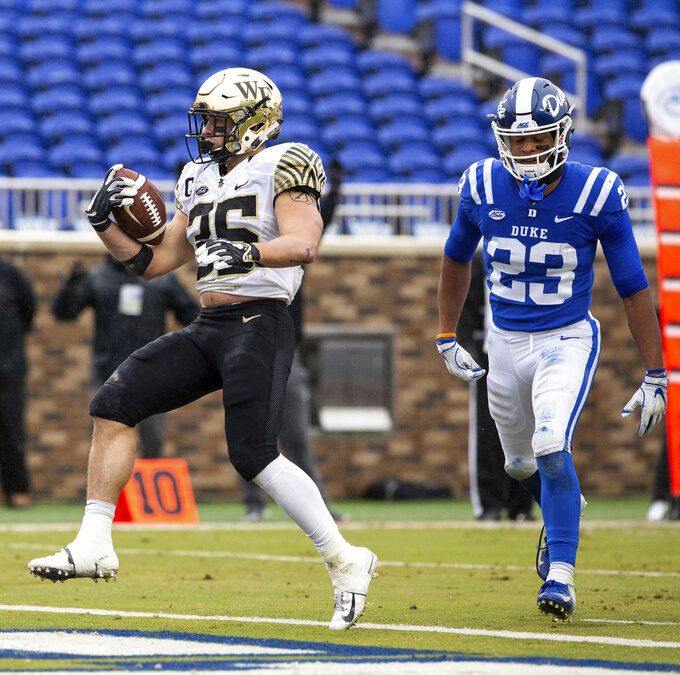 Wake Forest's Willy Bemiss (35) scores a touchdown ahead of Duke's Lummie Young IV (23) during the first half of an NCAA college football game in Durham, N.C., Saturday, Nov. 24, 2018. (AP Photo/Ben McKeown)
