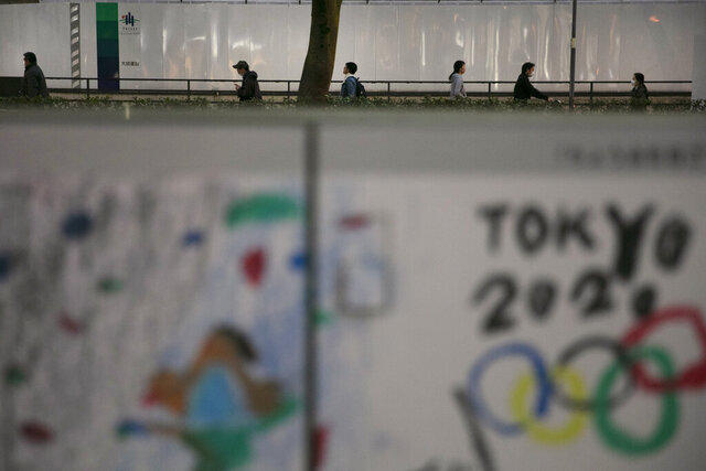 FILE - In this March 3, 2020, file photo, commuters walk along a sidewalk as a poster celebrating the Tokyo 2020 Olympics is seen in foreground in Tokyo. The tentacles of cancelling the Tokyo Olympics — or postponing or staging it in empty venues — would reach into every corner of the globe, much like the spreading virus that now imperils the opening ceremony on July 24. (AP Photo/Jae C. Hong, File)