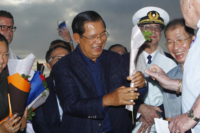 Cambodia's Prime Minister Hun Sen, center, gives a flower to a passenger who disembarked from the MS Westerdam, owned by Holland America Line, at the port of Sihanoukville, Cambodia, Friday, Feb. 14, 2020. Hundreds of cruise ship passengers long stranded at sea by virus fears cheered as they finally disembarked Friday and were welcomed to Cambodia. (AP Photo/Heng Sinith)