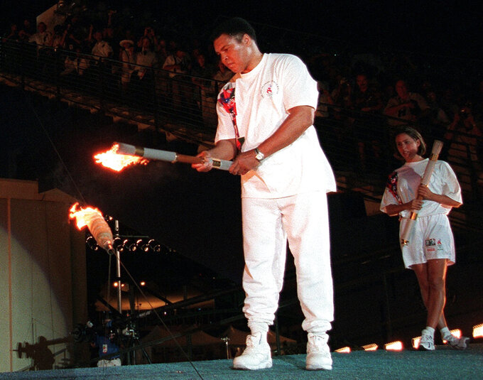 FILE - In this July 19, 1996, file photo, American swimmer Janet Evans , right, looks on as Muhammad Ali lights the Olympic flame during the 1996 Summer Olympic Games opening ceremony in Atlanta. (AP Photo/Michael Probst, File)