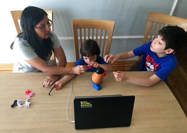In this May 21, 2020, photo, Pablo Prengaman, center, practices recognizing and verbalizing body parts while building a Mr. Potato Head with the help of mother, Lorena Prengaman, and brother Lucas Prengaman, during a speech therapy session via Zoom in Phoenix. Pablo, who is 4 years old and has Down syndrome, has been doing online speech and occupational therapies since March because of the coronavirus pandemic. (AP Photo/Peter Prengaman)