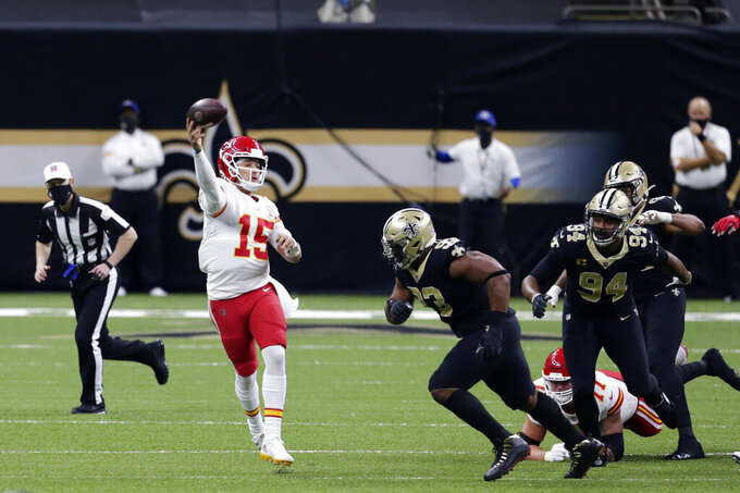 Kansas City Chiefs quarterback Patrick Mahomes (15) passes under pressure from New Orleans Saints defensive tackle David Onyemata (93) and defensive end Cameron Jordan (94) in the first half of an NFL football game in New Orleans, Sunday, Dec. 20, 2020. (AP Photo/Butch Dill)