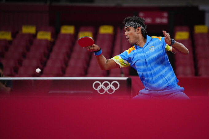 India's Achanta Kamal competes during the table tennis men's singles third round match against China's Ma Long at the 2020 Summer Olympics, Tuesday, July 27, 2021, in Tokyo. (AP Photo/Kin Cheung)