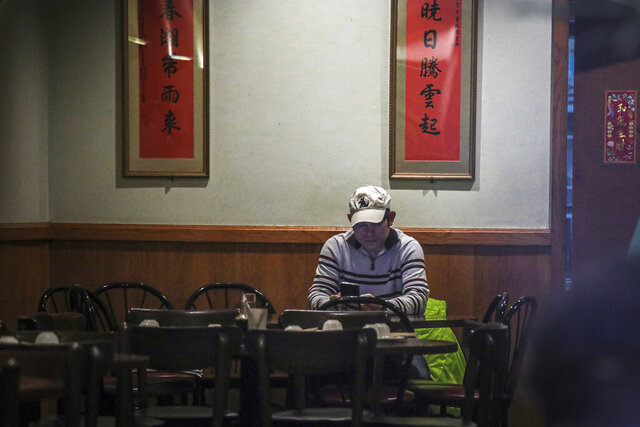 In this Feb. 13, 2020, photo, Frankie Chu, owner of Vegetarian Dim Sum House in New York's Chinatown, sits in his empty restaurant usually bustling with customers, in New York. Sales have plunged 70% over the last two weeks,