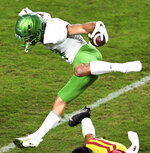 Oregon wide receiver Mycah Pittman catches a pass and leaps over USC cornerback Chris Steele for a first down in the first half of an NCAA college football game at the Los Angeles Memorial Coliseum in Los Angeles on Friday, Dec. 18, 2020. (Keith Birmingham/The Orange County Register via AP)