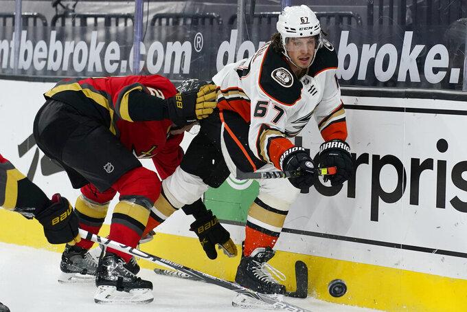 Anaheim Ducks center Rickard Rakell (67) passes around Vegas Golden Knights defenseman Zach Whitecloud (2) during the third period of an NHL hockey game Tuesday, Feb. 9, 2021, in Las Vegas. (AP Photo/John Locher)