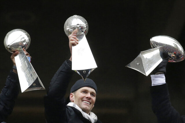 FILE - In this Feb. 7, 2017, file photo, New England Patriots quarterback Tom Brady holds a Super Bowl trophy beside others the team previously had won during a rally in Boston to celebrate the team's 34-28 win over the Atlanta Falcons in the NFL Super Bowl 51 football game in Houston. If Tom Brady isn't a unanimous selection to the All-Decade team, it will be a bigger upset than the Jets over the Colts in Super Bowl 3. Next Monday, April 6, 2020, the Hall of Fame and the NFL will announce the roster for the 2010-19 span. (AP Photo/Elise Amendola, File)