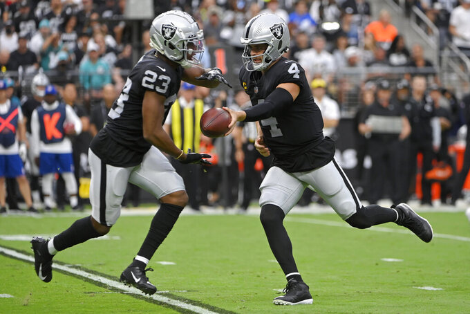 Las Vegas Raiders quarterback Derek Carr (4) hands off to running back Kenyan Drake (23) against the Miami Dolphins during the first half of an NFL football game, Sunday, Sept. 26, 2021, in Las Vegas. (AP Photo/David Becker)