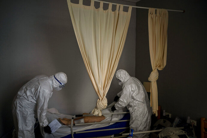 Wearing protective suits to prevent infection, mortuary workers prepare the body of an elderly person who died of COVID-19 before removing it from a nursing home in Barcelona, Spain, Friday, Nov. 13, 2020. After successfully bringing the daily death count down from over 900 in March to single digits by July, Spain has seen a steady uptick that brought deaths back to over 200 a day this month. With that relapse, the body collectors have returned to making the rounds of hospitals, homes and care facilities. (AP Photo/Emilio Morenatti)